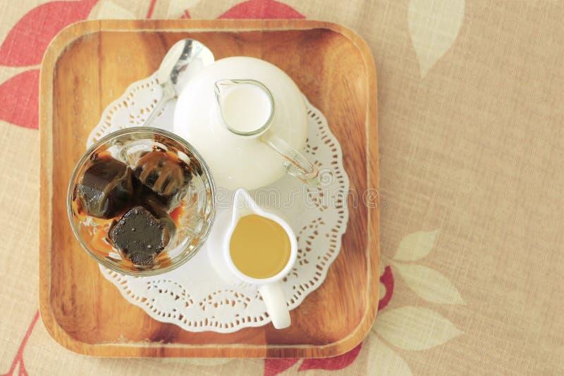 Gefrorener Kaffeewürfel mit frischer Milch und Sirup auf Tischdecke mit Co stockfotos