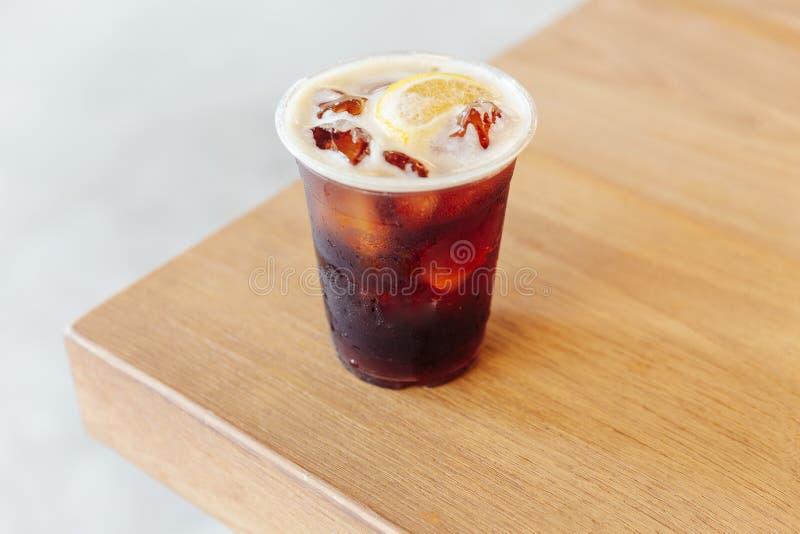 Gefrorener kalter Gebräunitrokaffee mit Zitrone auf Holztisch lizenzfreies stockbild