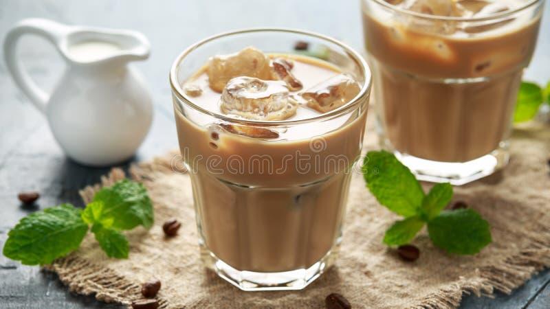 Gefrorener Lattekaffee in einem Glas mit kalter Milch Orange und Carafe mit Zitrusfruchteiswasser stockbilder