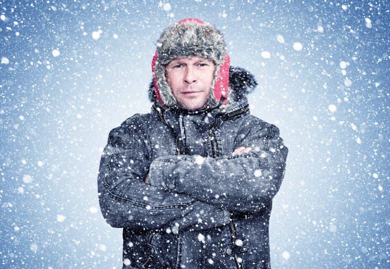 Gefrorener Mann in einem Mantel mit Schafshaut, der seine Hände erwärmt, kalt, Schnee, Frost, Blizzard stockfoto