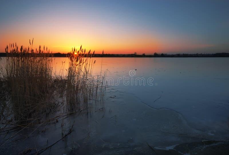 Gefrorener See am Sonnenuntergang lizenzfreie stockbilder
