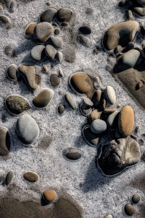 Gefrorener Stein auf Westküsten-Strand lizenzfreie stockfotos