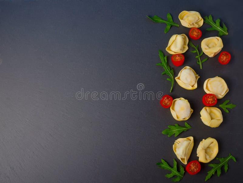 Gefrorener Tortellini auf dem schwarzen Hintergrund Italienischer Tortellini mit frischen Ricottablättern und -tomaten auf einem  stockfoto