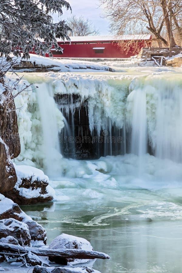 Gefrorener Wasserfall und überdachte Brücke stockfoto