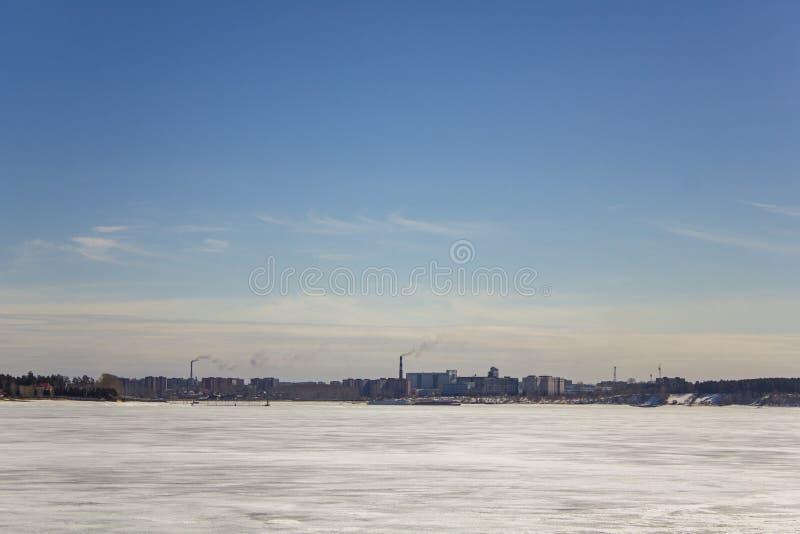 Gefrorener weißer Schneesee auf dem Hintergrund der Stadt mit hohen Gebäuden und rauchenden enormen Rohren unter einem klaren b lizenzfreies stockfoto