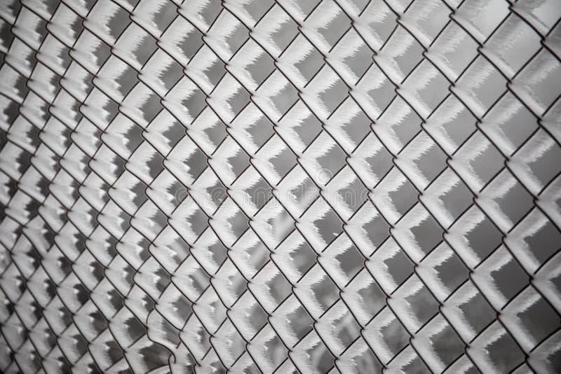 Gefrorener Zaun hergestellt von der Metallmasche umfasst mit Frostkristallen, ein früher sonniger kalter Morgen, auf einem unscha stockbilder