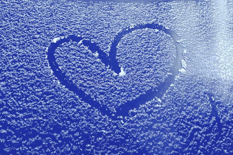 Gefrorenes Glas eines Autos an einem Wintertag, zeichnendes Herz stockfotos