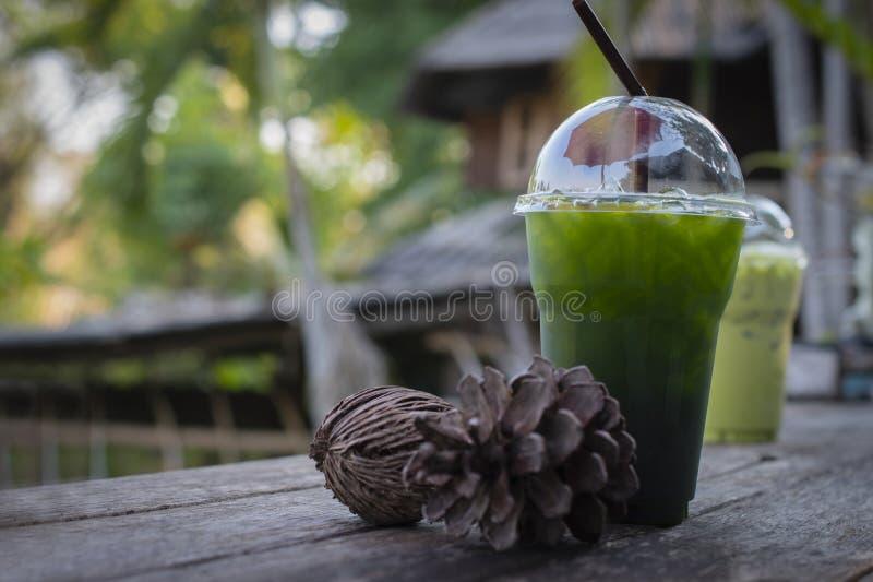 Gefrorenes Honigzitronengetränk des grünen Tees mit getrockneten Kiefernkegeln auf Holztisch gegen alten Hintergrund des hölzerne stockfotos