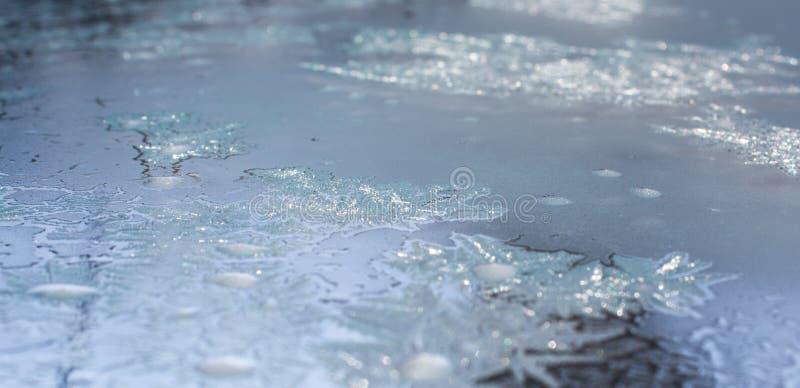 Gefrorenes Wasser auf dem Fenster stellt silberne Dekorationsverzierungen her stockfoto