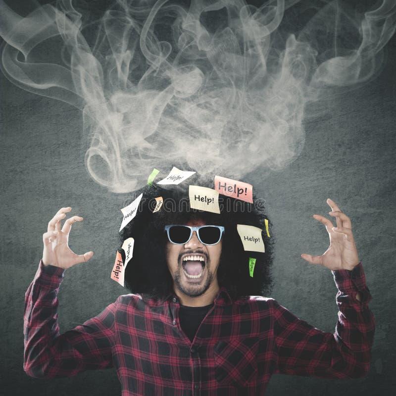 Gefrustreerde Afro-mens met rook op hoofd stock fotografie