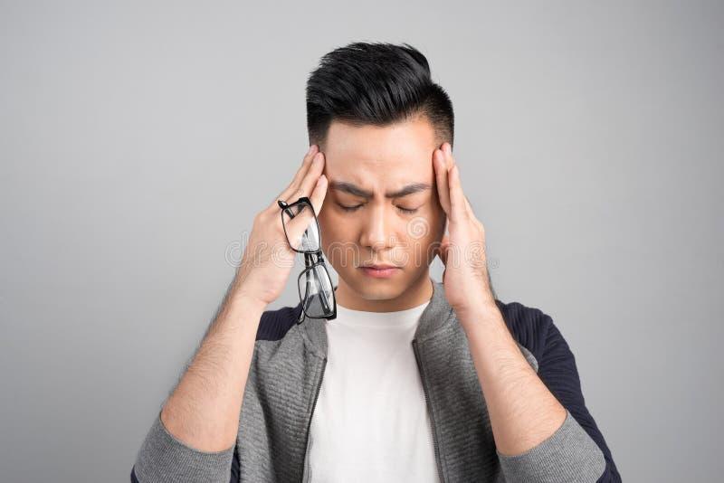 Gefrustreerde bedrijfs Aziatische mens met een hoofdpijn - die over gr. wordt geïsoleerd stock afbeelding