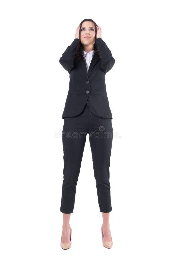 Gefrustreerde bedrijfsvrouw in kostuum met handen die oren behandelen die omhoog eruit zien royalty-vrije stock foto