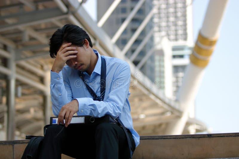 Gefrustreerde beklemtoonde Aziatische zakenman met hand op voorhoofdzitting op trap in de stad Gedeprimeerde conc werkloosheidsza royalty-vrije stock afbeeldingen
