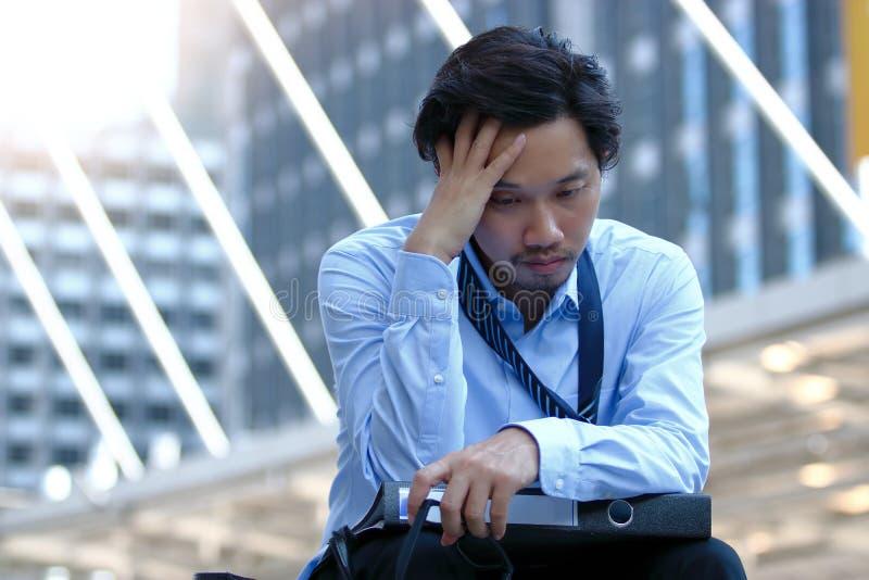 Gefrustreerde beklemtoonde jonge Aziatische bedrijfsmens wat betreft vermoeid of droevig hoofd en voelen zijn baan stock fotografie