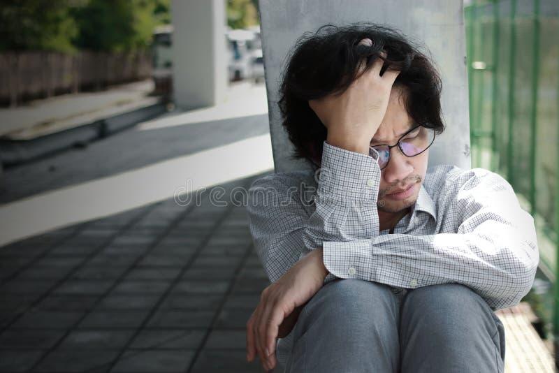 Gefrustreerde beklemtoonde jonge Aziatische mens wat betreft teleurgesteld of uitgeput hoofd en voelen Werkloos zakenmanconcept royalty-vrije stock foto's