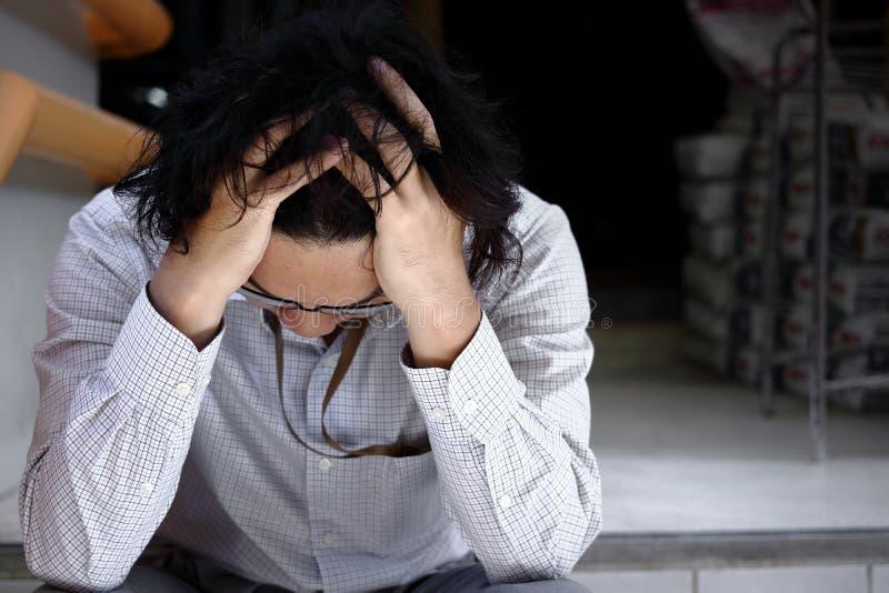 Gefrustreerde beklemtoonde jonge Aziatische mens wat betreft teleurgesteld of uitgeput hoofd en voelen Werkloos zakenmanconcept stock foto