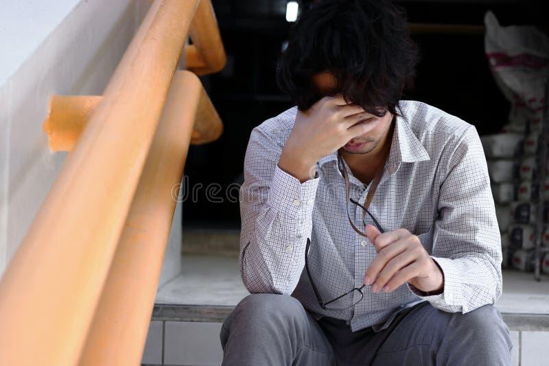 Gefrustreerde beklemtoonde jonge Aziatische mens wat betreft teleurgesteld of uitgeput hoofd en voelen Werkloos zakenmanconcept stock afbeeldingen