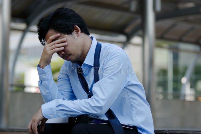 Gefrustreerde beklemtoonde jonge Aziatische zakenman wat betreft hoofd en voelen vermoeid en uitgeput met zijn baan royalty-vrije stock fotografie