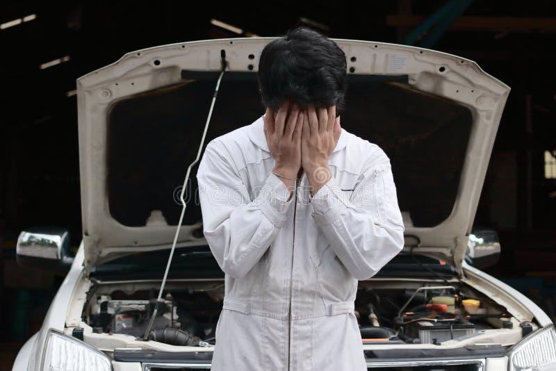 Gefrustreerde beklemtoonde jonge mechanische mens in witte eenvormig behandelend zijn gezicht met handen tegen auto in open kap b stock fotografie