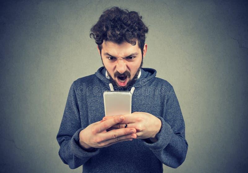 Gefrustreerde boze mens die een tekstbericht op zijn gefrustreerd smartphonegevoel lezen royalty-vrije stock foto