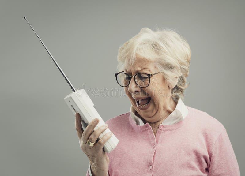 Gefrustreerde hogere vrouw die een oude telefoon met behulp van royalty-vrije stock afbeeldingen