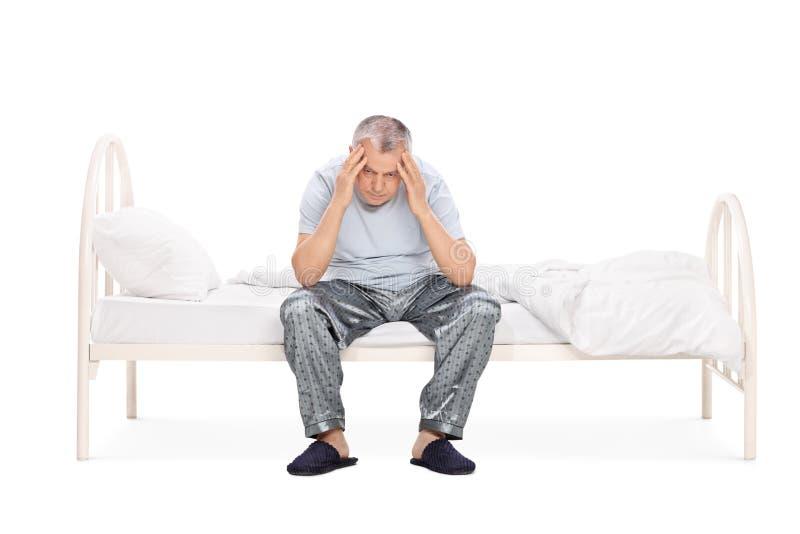 Gefrustreerde hogere zitting op een bed in zijn pyjama's stock afbeeldingen