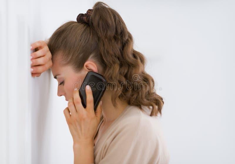 Gefrustreerde jonge vrouw die mobiele telefoon spreken royalty-vrije stock afbeelding