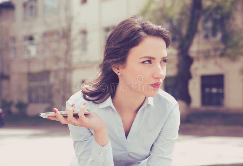 Gefrustreerde jonge vrouw die op een telefoongesprek van haar vriendzitting buiten wachten in de straat royalty-vrije stock afbeeldingen