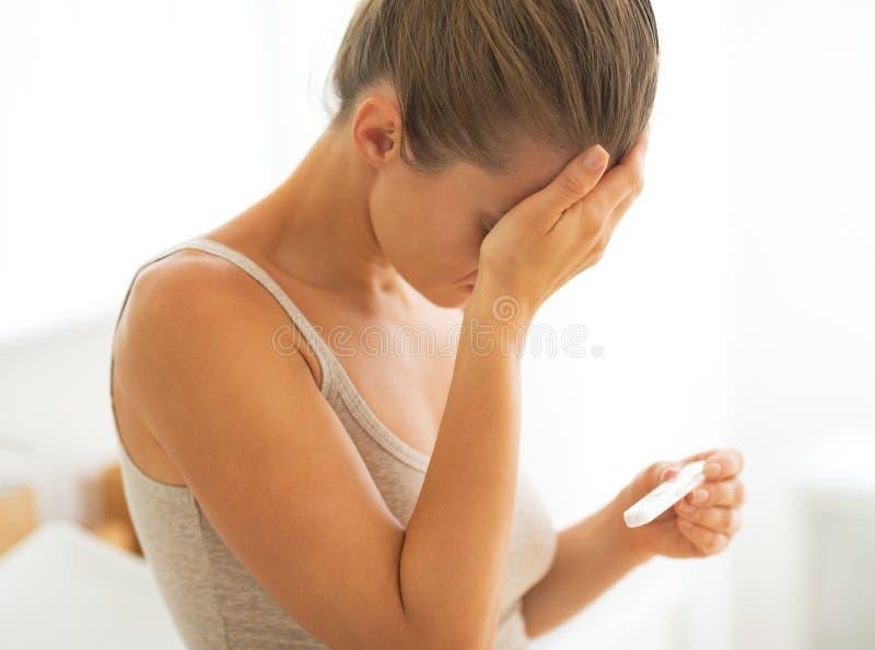 Gefrustreerde jonge vrouw met zwangerschapstest stock afbeeldingen