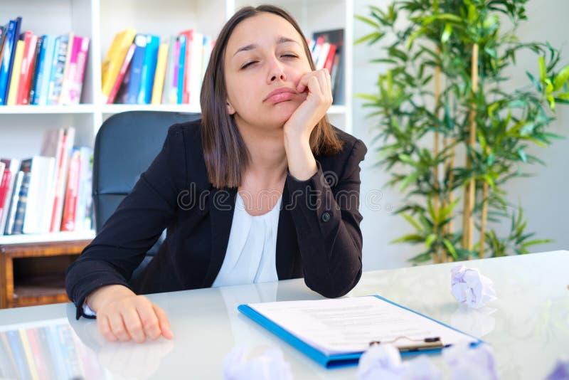 Gefrustreerde jonge vrouw op haar werkende plaats in bureau royalty-vrije stock foto