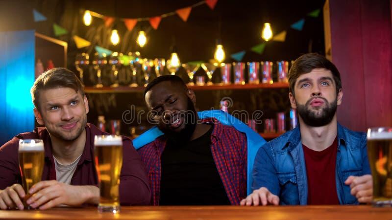 Gefrustreerde mannelijke die vrienden met einde van reeks zij worden verstoord die in bar letten op stock fotografie