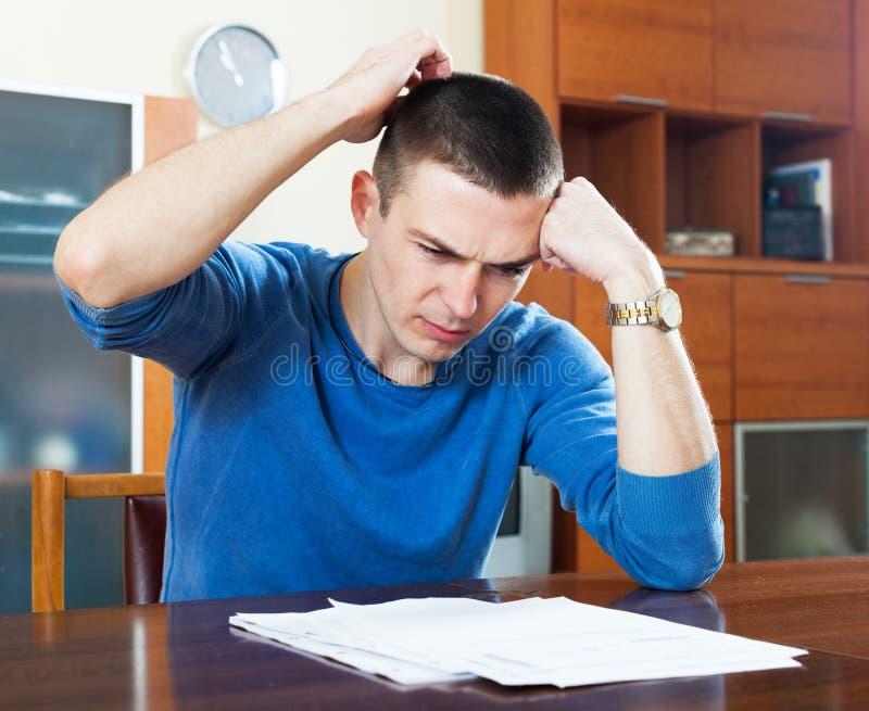 Gefrustreerde mens die financieel document bekijken stock afbeeldingen