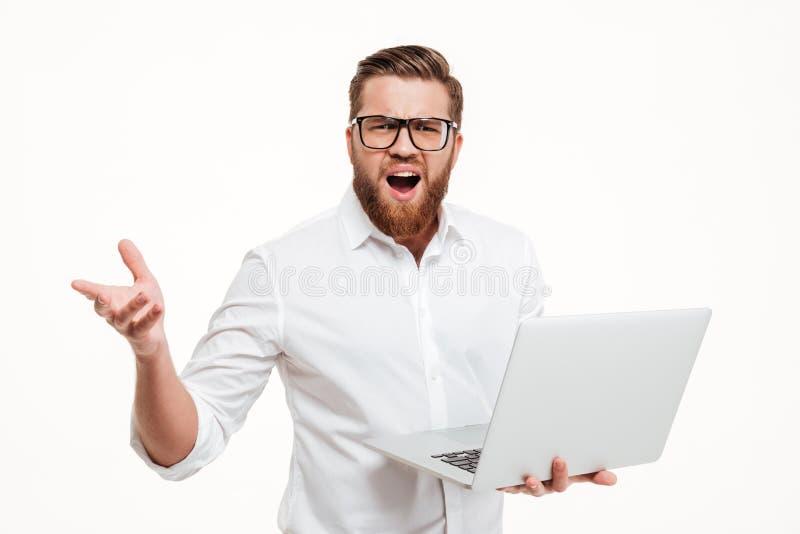 Gefrustreerde mens in oogglazen die laptop houden en met hand gesturing royalty-vrije stock afbeeldingen