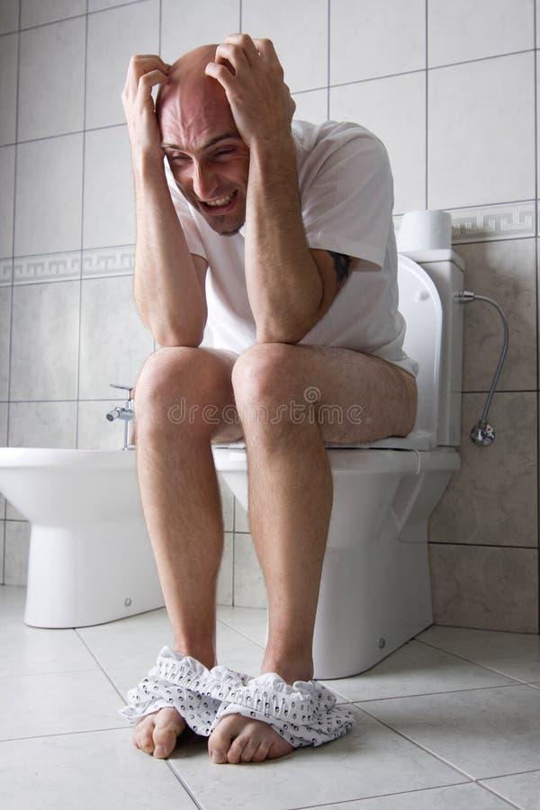 Gefrustreerde mens op toiletzetel royalty-vrije stock foto