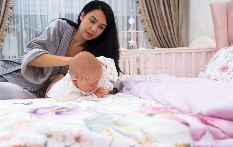 Gefrustreerde moeder kledende baby in de ochtend stock foto's
