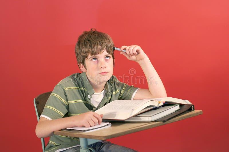 Gefrustreerde student bij zijn bureau royalty-vrije stock fotografie