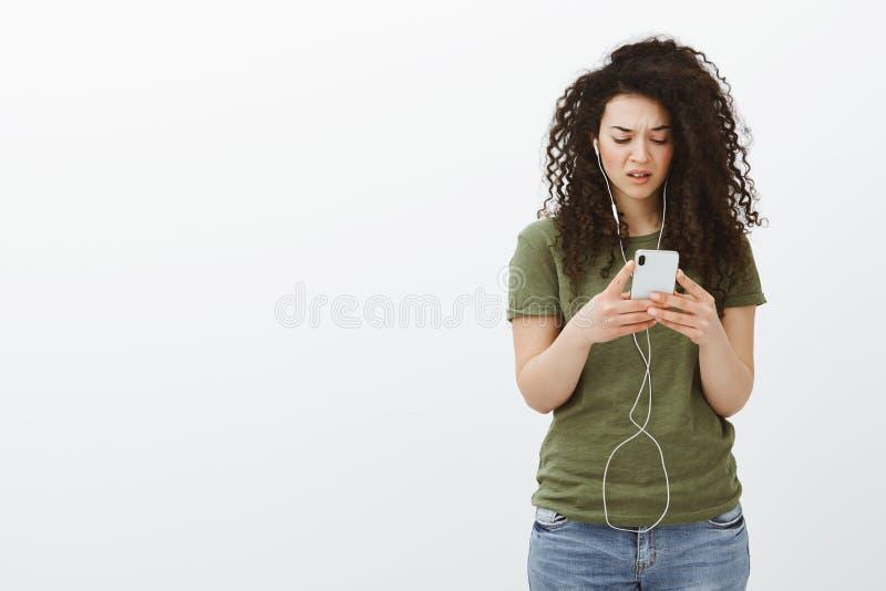 Gefrustreerde vrouw die bij smartphone cluelessly staren Portret van verward ontstemd krullend-haired meisje in toevallige uitrus royalty-vrije stock afbeeldingen
