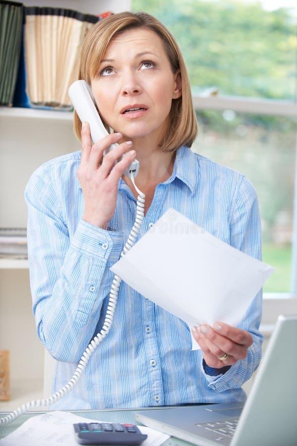 Gefrustreerde Vrouw op Telefoon in Huisbureau stock afbeelding