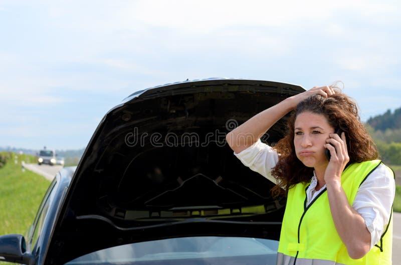 Gefrustreerde vrouwelijke bestuurder die hulp verzoeken stock foto