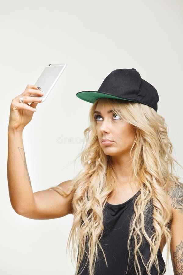 Gefrustreerde vrouwelijke emotie in de telefoon van de blondeholding bij bovenkant over geïsoleerd wit Gebrek aan mededeling of I royalty-vrije stock foto