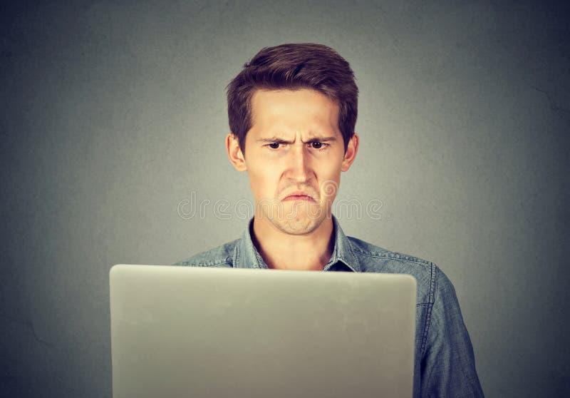 Gefrustreerde weerzinwekkende mens die niet bevallen laptop bekijken stock foto
