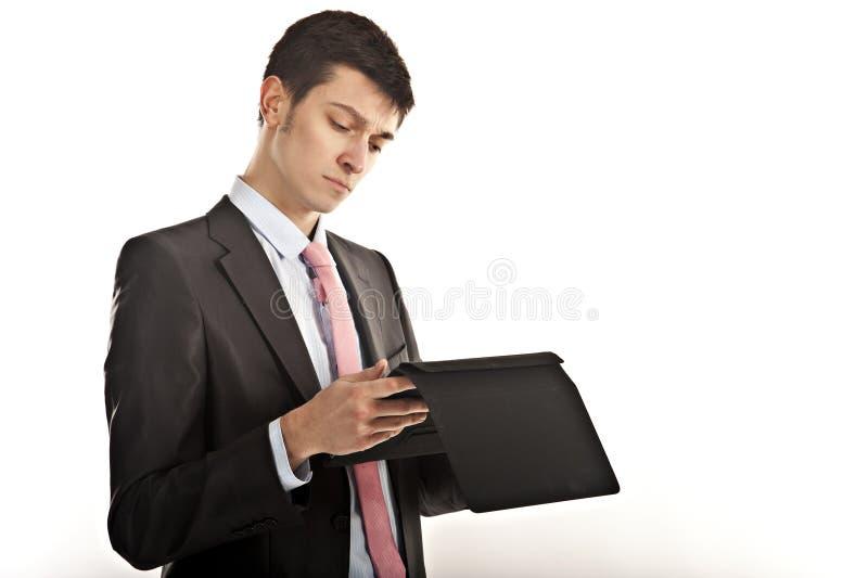 Gefrustreerde zakenman die zijn computertablet bijt royalty-vrije stock foto's