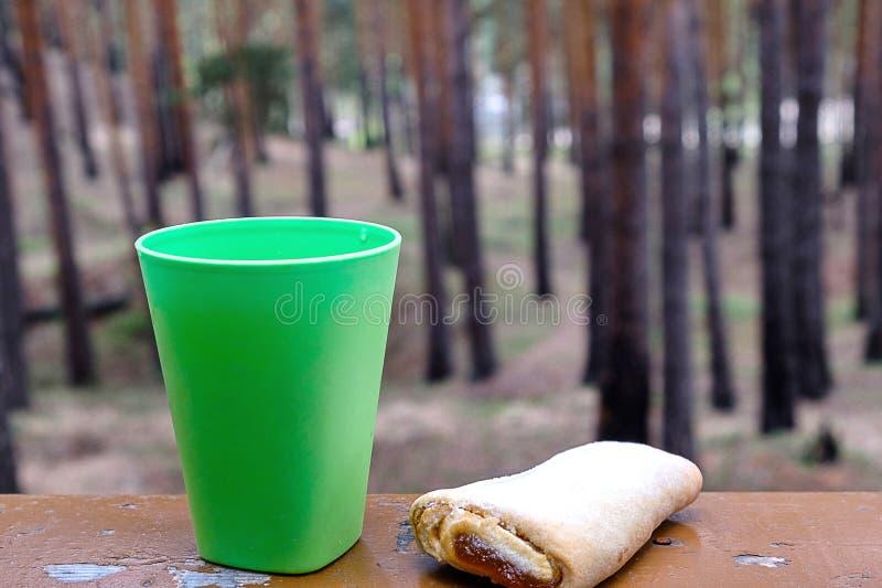 Gegen einen Hintergrund eines Kiefernwaldes ein grünes Plastikglas mit Tee und einem Plätzchen auf einem hölzernen stockfotos