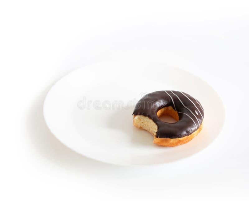 Gegeten die chocoladedoughnut op witte achtergrond wordt ge?soleerd de doughnut is gebeten op plaat royalty-vrije stock afbeelding