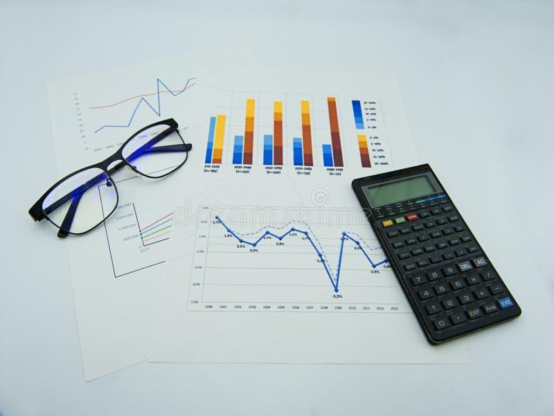Gegevensgrafieken en diagrammen, glazen en calculator, witte achtergrond royalty-vrije stock foto