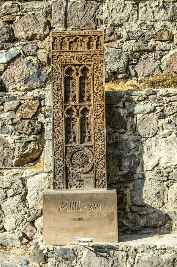 Copy of a carved medieval khachkar from Jugha,installed along a steep road,near a stone-paved wall leading to the Monastery of Geg stock image