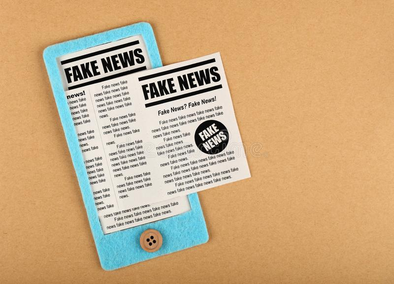 Geglaubter Handwerk Smartphone mit GEFÄLSCHTEN NACHRICHTEN-Zeitungen lizenzfreie stockfotografie