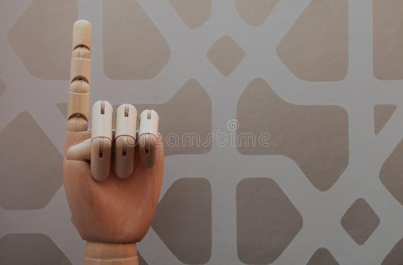 Gegliederte hölzerne Hand mit einem Finger hob in Anspielung auf Nummer Eins an stockbilder