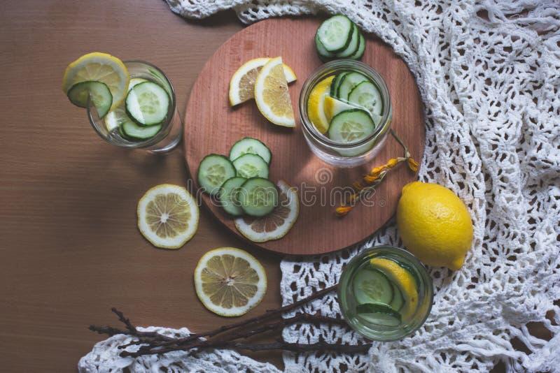 Gegoten citroen en komkommerwater stock afbeeldingen