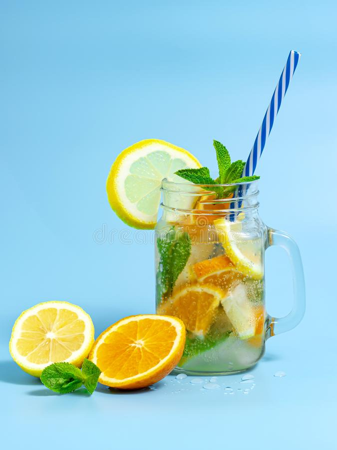 Gegoten detox geef met ijs, citroen en sinaasappelenplakken met munt op blauwe achtergrond water Bevroren koude de zomercocktail  royalty-vrije stock foto